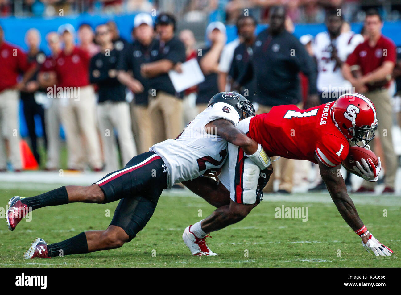 Charlotte, NC, USA. 2nd Sep, 2017. D.J. Smith (24) of the South Carolina Gamecocks wraps up Jaylen Samuels (1) of the NC State Wolfpack as he reaches for the first down but comes up short in the NCAA football matchup between the NC State Wolfpack and the South Carolina Gamecocks at Bank of America Stadium in Charlotte, NC. (Scott Kinser/Cal Sport Media) Credit: csm/Alamy Live News - Stock Image