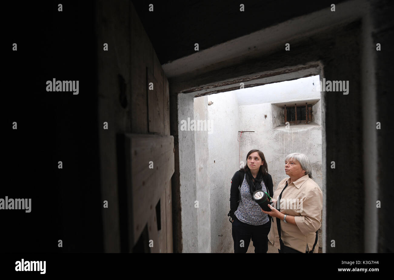 Frankenberg, Germany. 23rd Aug, 2071. FILE - Archival material shows Gisela Heiden (R) and Anna Schueller using torches to look at inscriptions in a cell in the former concentration camp Sachsenburg in Frankenberg, Germany, 23 August 2071. The Nazi organisations SA and SS imprisoned more than 2000 critics of the regime in the former spinning mill between 1933 and 1937. The political parties Die Linke (Left Party) and Die Gruenne (Alliance 90/The Greens) plan to transform the factory into a memorial. Photo: Hendrik Schmidt/dpa-Zentralbild/ZB/dpa/Alamy Live News - Stock Image
