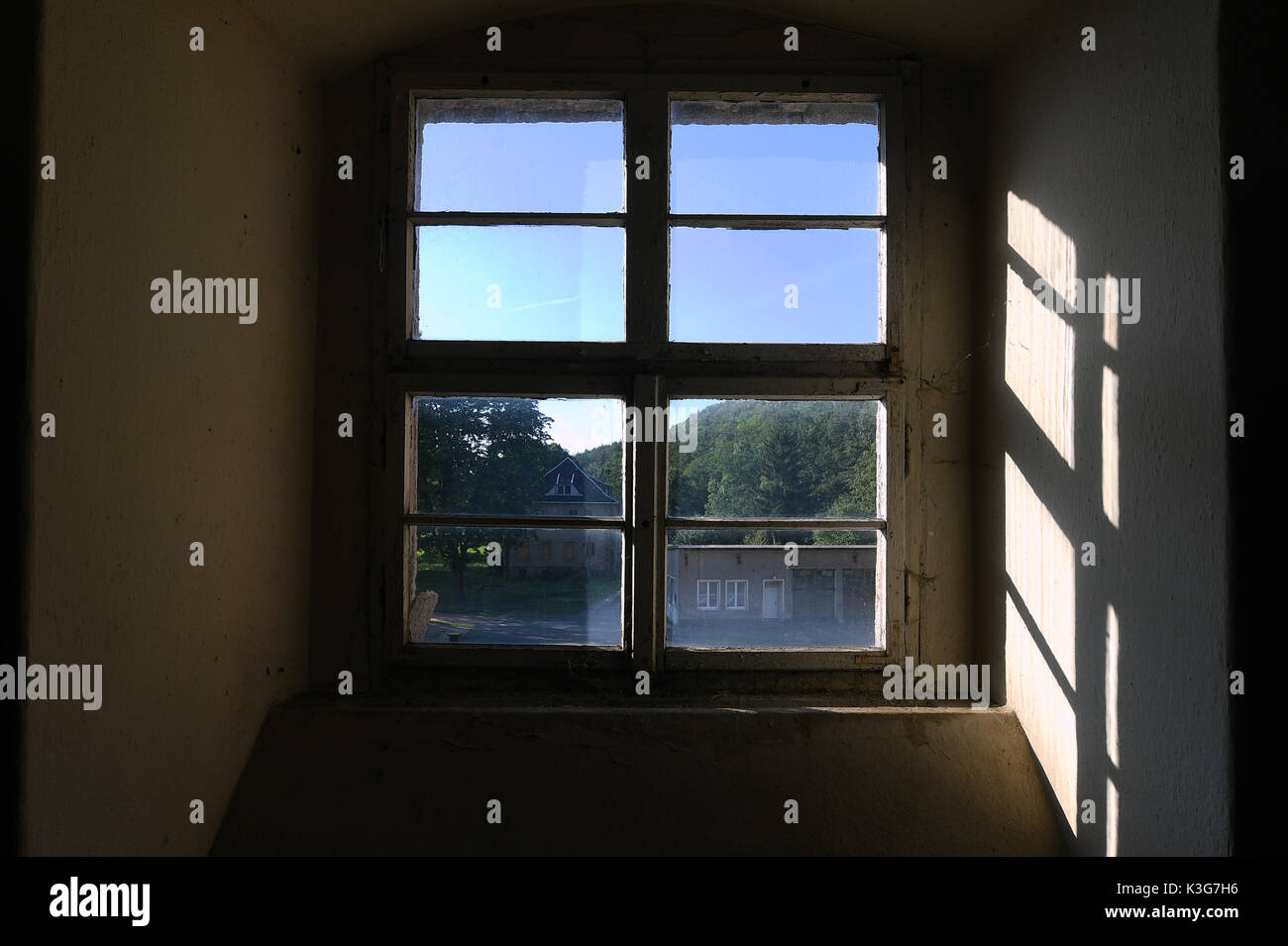 Frankenberg, Germany. 23rd Aug, 2071. FILE - Archival material shows the window of a factory room that served as chamber for prisoners in the former concentration camp Sachsenburg in Frankenberg, Germany, 23 August 2071. To the left the villa of the commander is visible. The Nazi organisations SA and SS imprisoned more than 2000 critics of the regime in the former spinning mill between 1933 and 1937. The political parties Die Linke (Left Party) and Die Gruenne (Alliance 90/The Greens) plan to transform the factory into a memorial. Photo: Hendrik Schmidt/dpa-Zentralbild/ZB/dpa/Alamy Live News - Stock Image