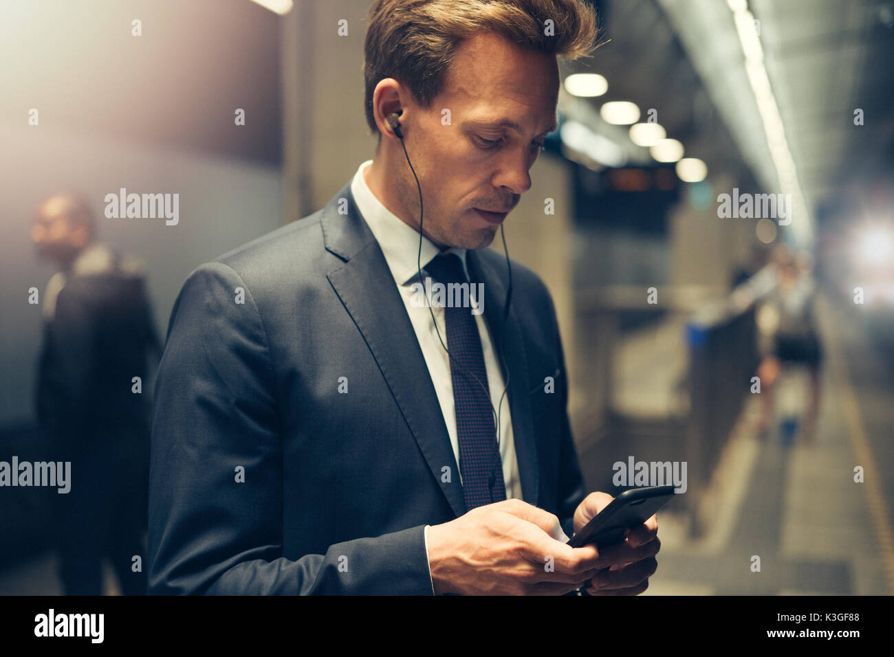 Young businessman wearing earphones and sending text messages on his cellphone while standing on a subway platform during his morning commute - Stock Image