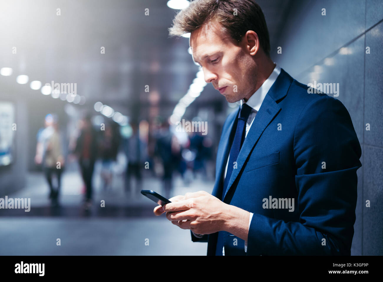 Young businessman standing on a subway platform during his morning commute reading text messages on his cellphone - Stock Image