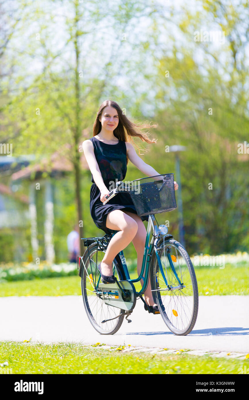 57fd64e8d1 Portrait view of girl on bicycle wearing on black short dress. Young happy  Woman riding