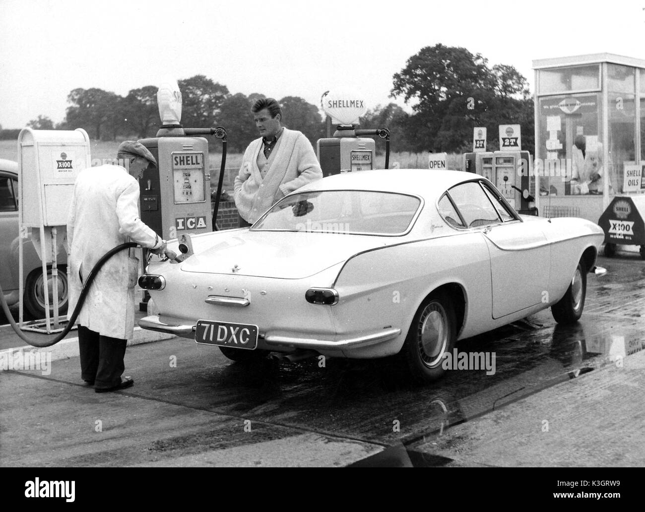 ROGER MOORE STAR OF THE SAINT WATCHING A GARAGE ATTENDANT FILL HIS VOLVO WITH PETROL - Stock Image
