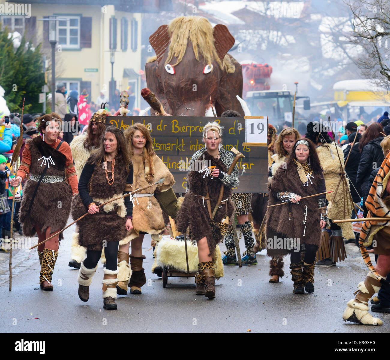 carnival procession on the high street of Bad Hindelang on carnival Sunday with many artistic masks, as for example primordial person close mammoth - Stock Image