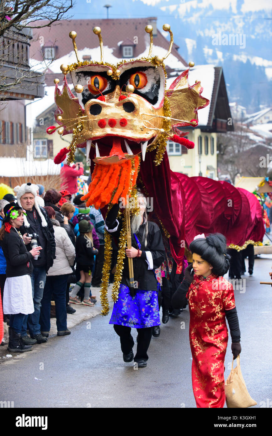 carnival procession on the high street of Bad Hindelang on carnival Sunday with many artistic masks, as for example Chinese dragon - Stock Image
