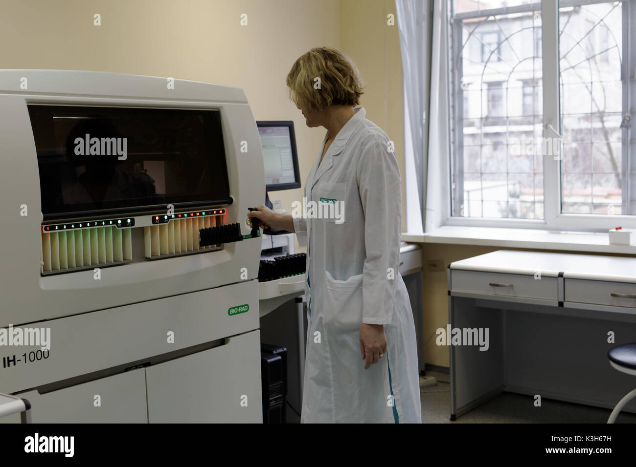 St. Petersburg, Russia - February 20, 2017: Laboratory analyst load the blood samples into the fully automated system for ID-cards in the city blood t - Stock Image