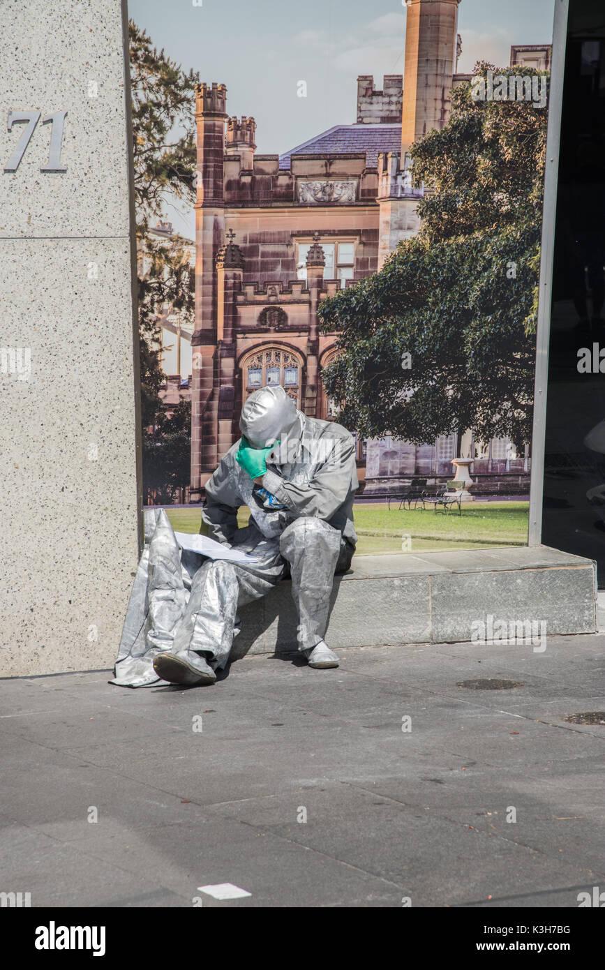 SYDNEY,NSW,AUSTRALIA-NOVEMBER 20,2016: Silver costumed street busker reading in solitude at the Circular Quay in Sydney, Australia - Stock Image