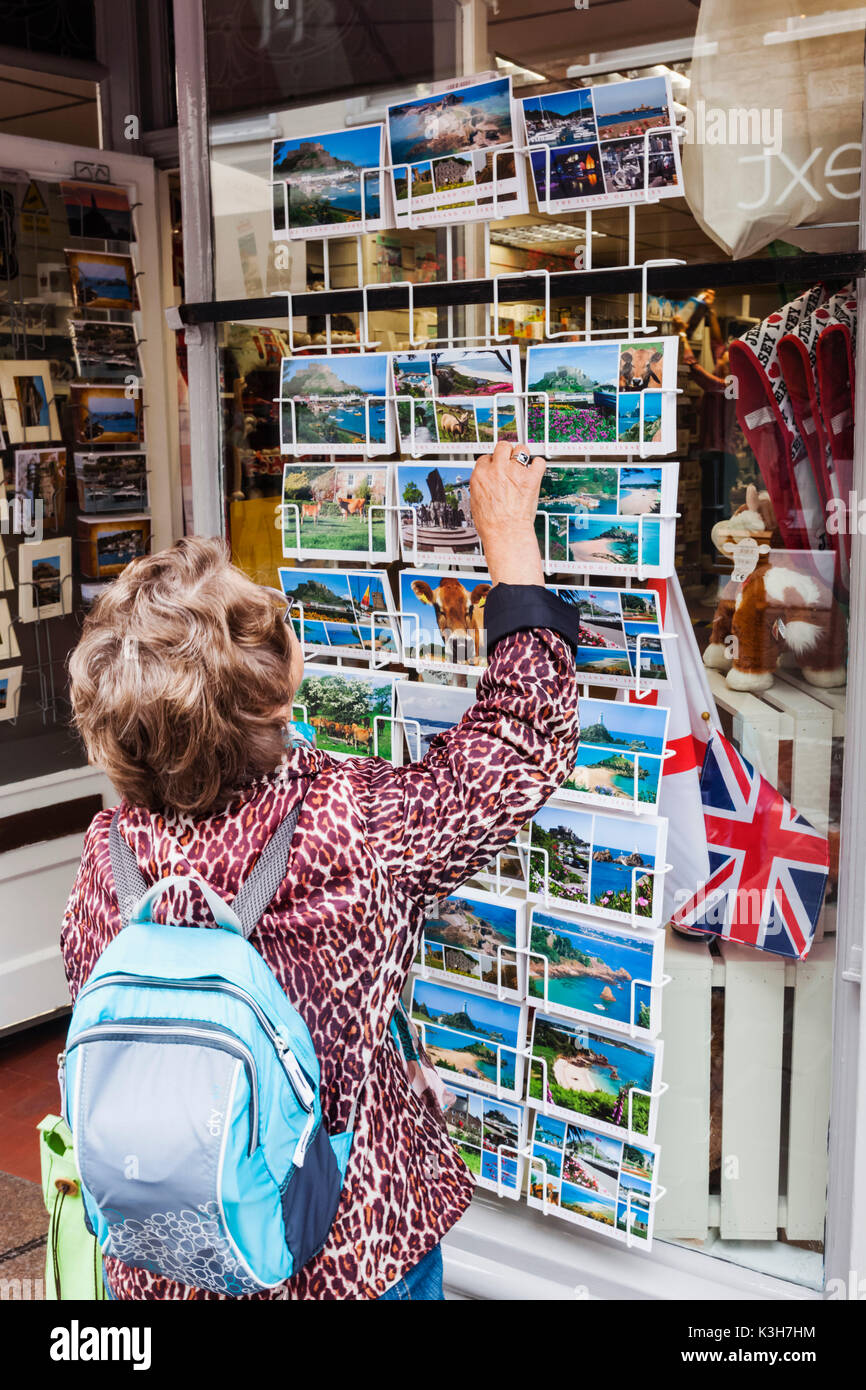 United Kingdom, Channel Islands, Jersey, St.Helier, King Street, Elderly Tourist Looking at Postcards - Stock Image