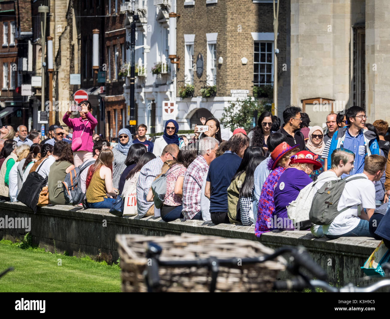 Cambridge Tourism - Tourists rest on a wall in front of  Kings College in Kings Parade in the historic centre of Cambridge UK - Stock Image