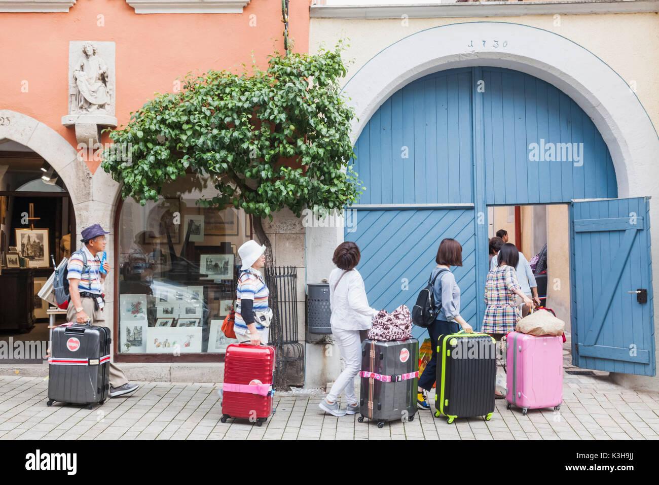 Germany, Bavaria, Romantic Road, Rothenburg-ob-der-Tauber, Asian Tourists Arriving Through Hotel Back Door - Stock Image