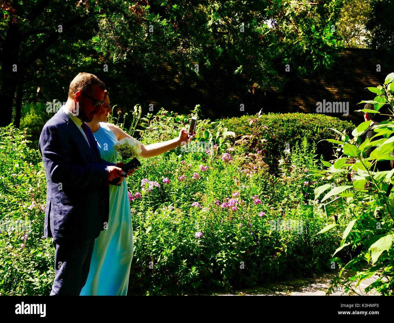 Couple, members of wedding party in fancy clothes, taking selfie in garden. Central Park, Manhattan, New York, NY, USA - Stock Image