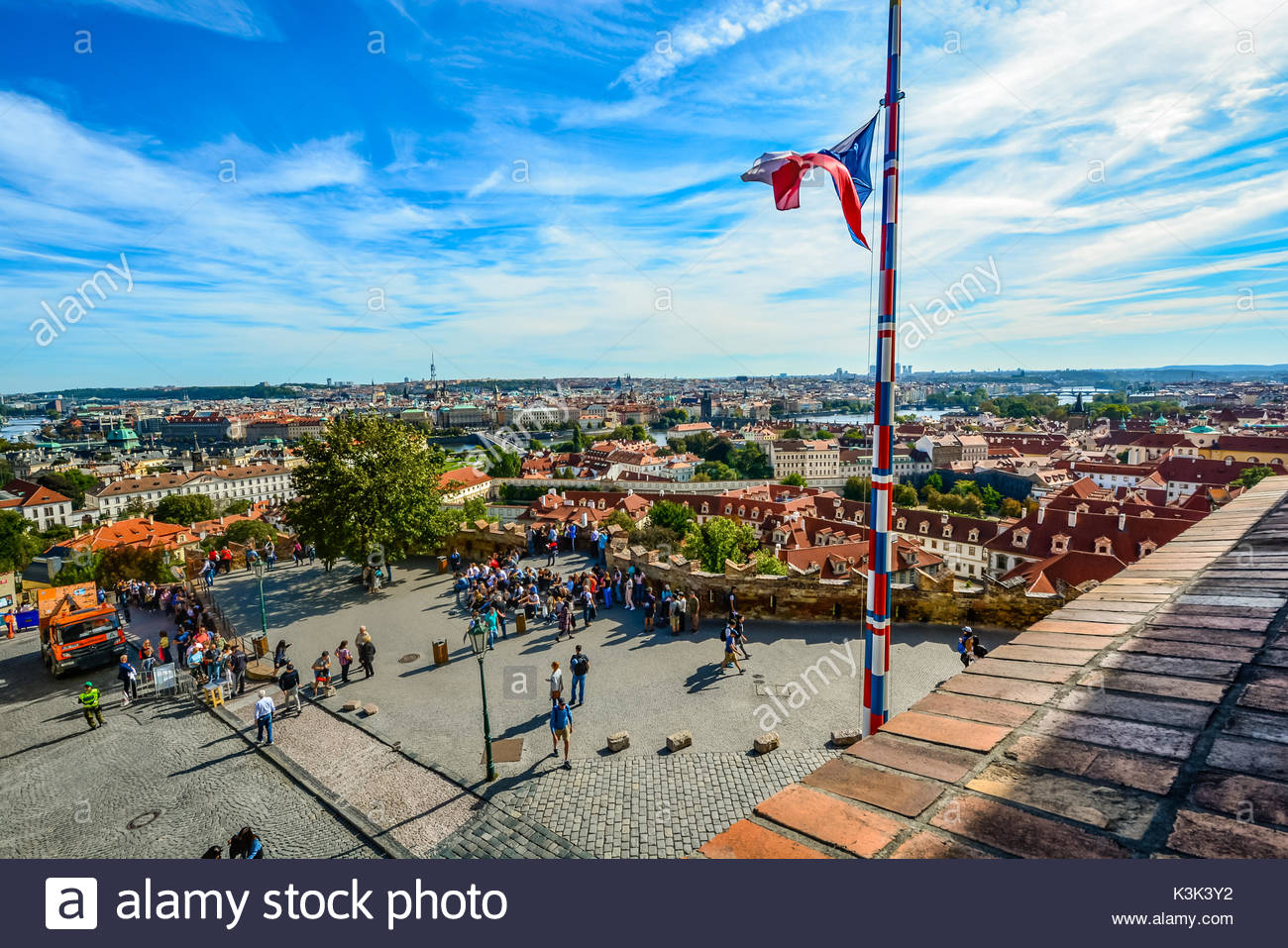 City view and skyline from atop the Prague Castle Complex with tourists below and a Czech flag flying on a flagpole - Stock Image