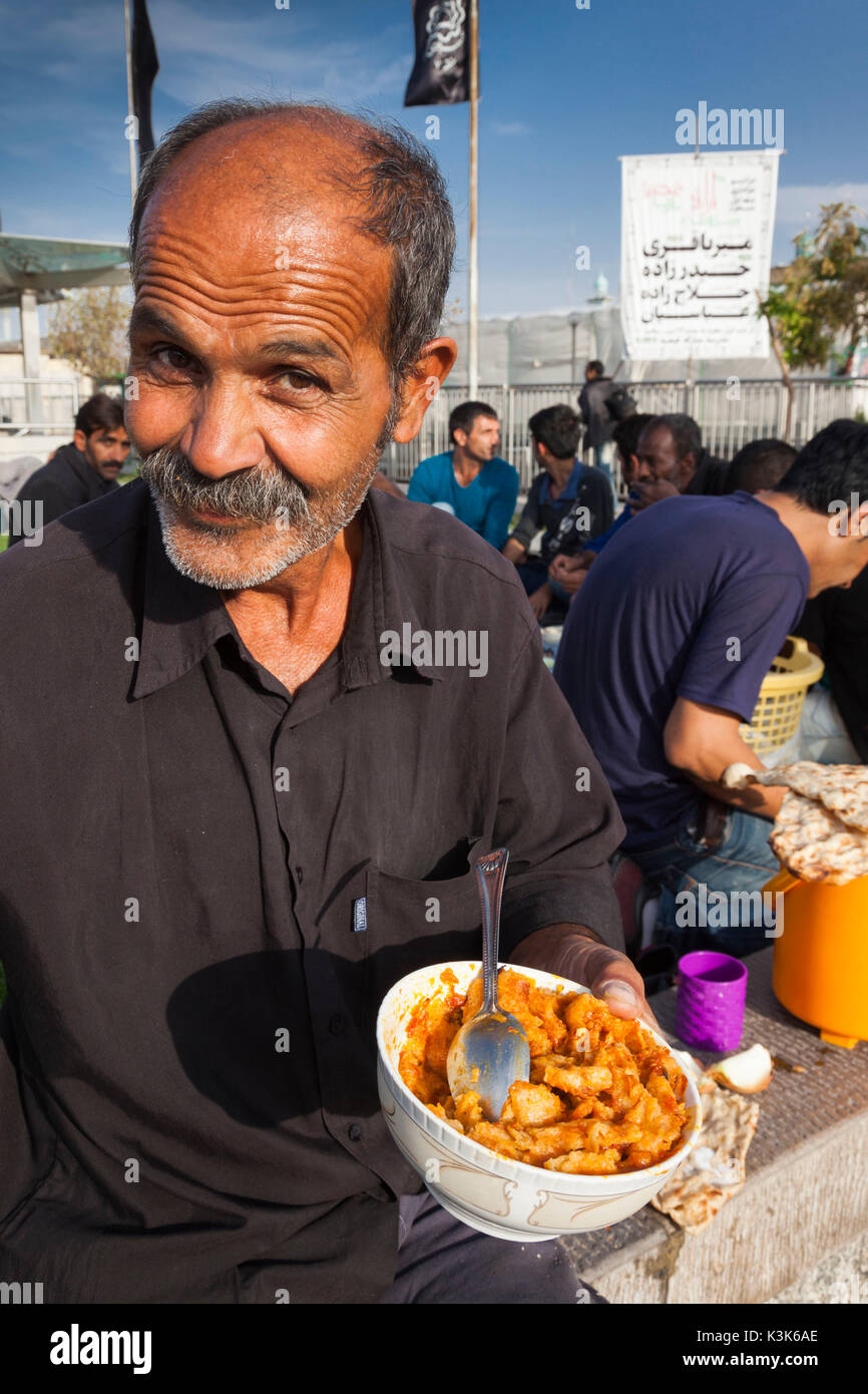 Iran, Central Iran, Qom, second holiest city in Iran after Mashad,  Hazrat-e Masumeh, Holy Shrine, burial place of Imam Reza's sister Fatemeh in the 9th century AD, religious pilgrim with food - Stock Image