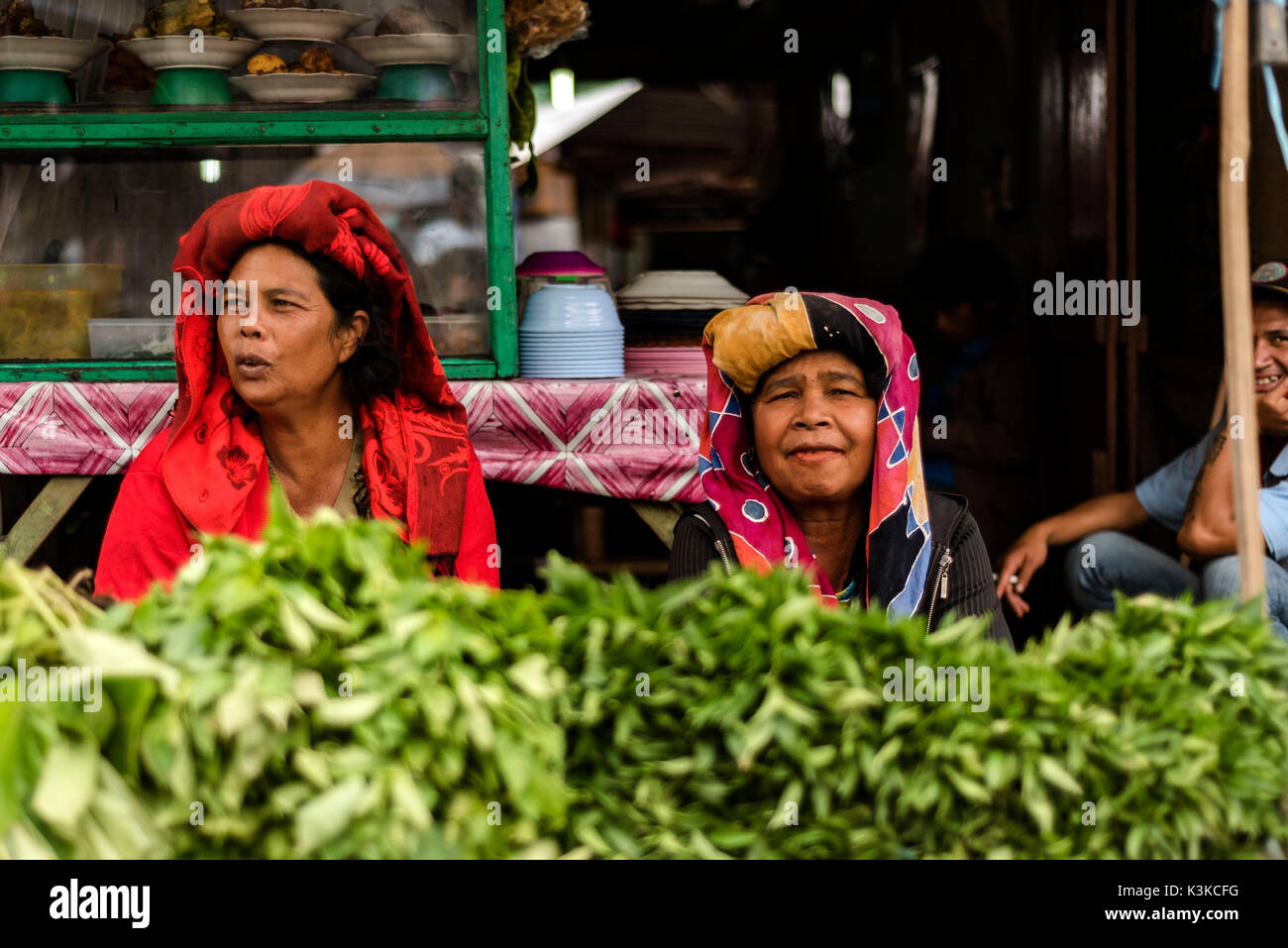 Two old market women in her vegetable stall, in traditional clothes of the Batak ethnic group. In the background there grins a smoking man. Recorded at the market in Berastagi on Sumatra, Indonesia. - Stock Image