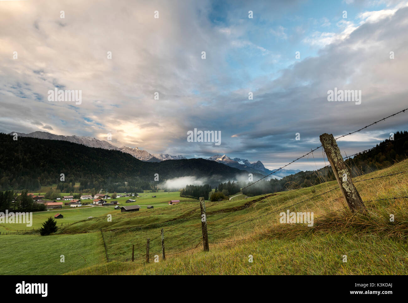 mossy pasture fence in a mountain pasture, in the background the hamlet Gerold, fog and clouds, as well as the Zugspitze massif in the morning light. - Stock Image