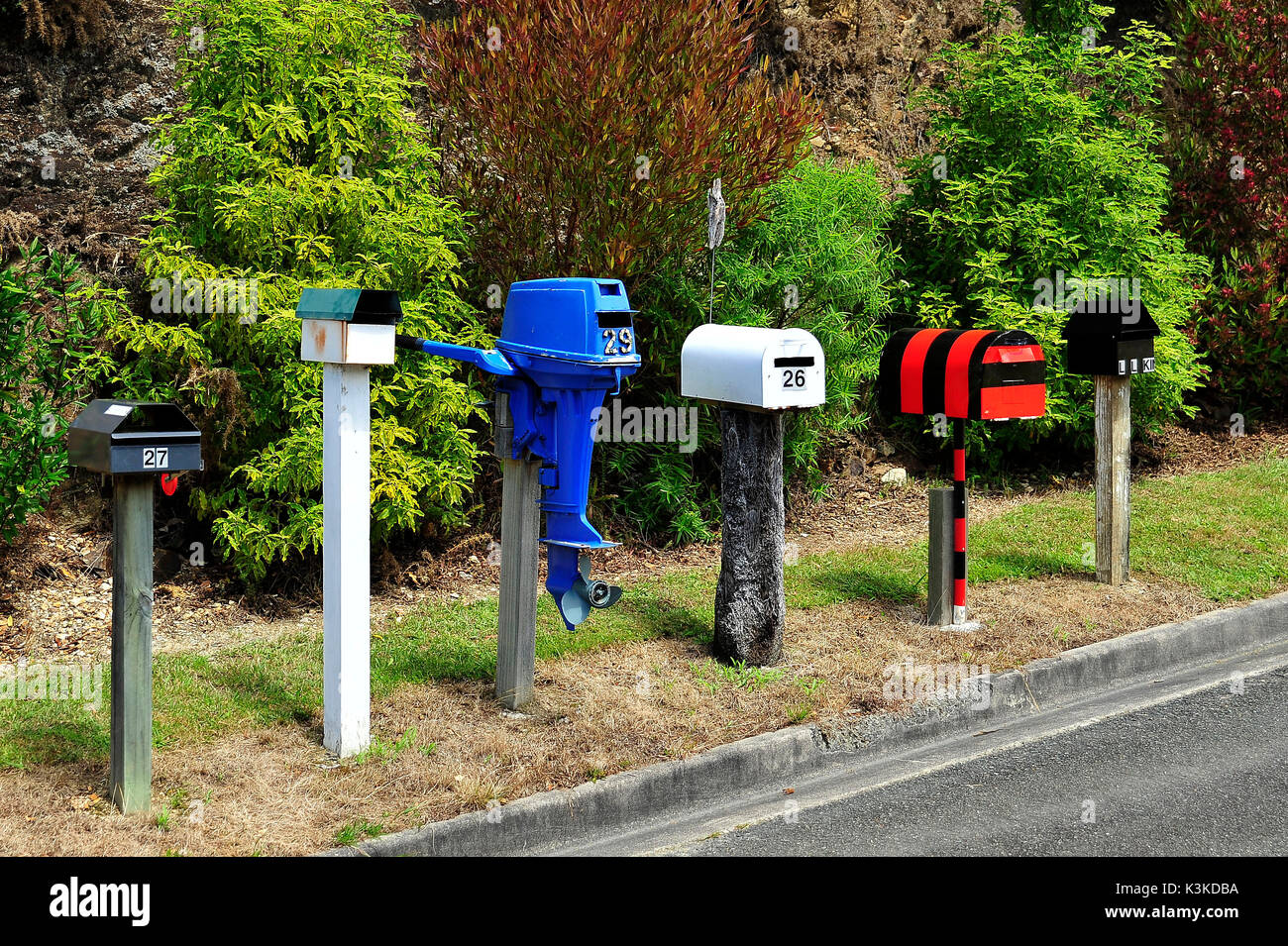 Coloured selfbuilt mailboxes, an old boot engine. - Stock Image