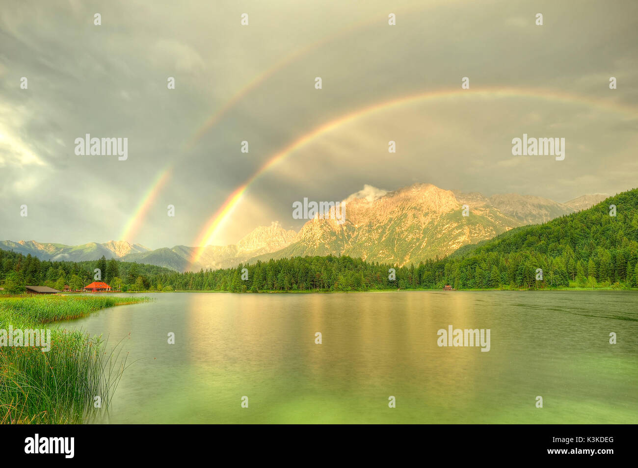 Double rainbow about the northern Karwendelgebirge (mountains) over Mittenwald. The water surface of the Lautersee (lake) is easily curled by beginning rain. On the left in the picture there is the red roof of a small outdoor swimming pool with kiosk, on the right the water guard small house. - Stock Image