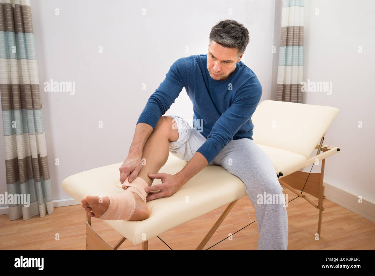 Man Sitting On Bed Typing Elastic Bandage To His Foot - Stock Image