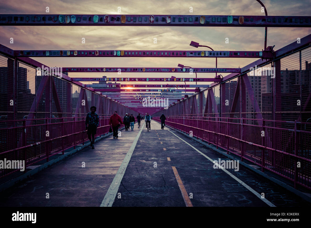 People and bicyclists at finishing time on Williamsburg Bridge, Sunset, New York, USA - Stock Image