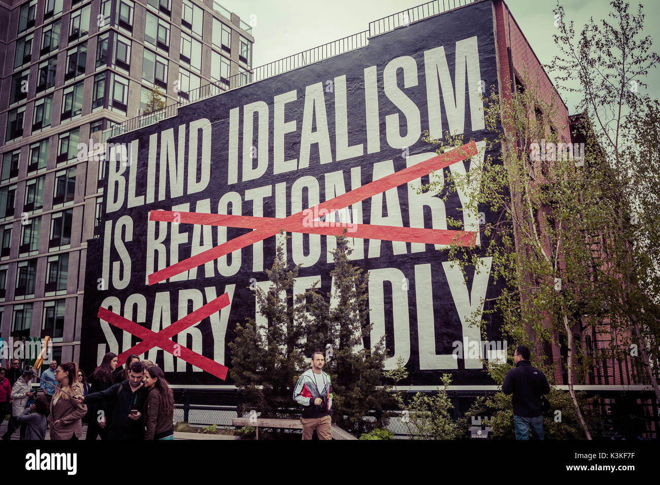 Billboard 'Blind Idealism is reactionary scary deadly', The High Line is a public park built on a historic freight rail line elevated above the streets on Manhattan's West Side. Chelsea, Art District, Tourist Attraction and Life Line of New York, Manhatten, USA - Stock Image