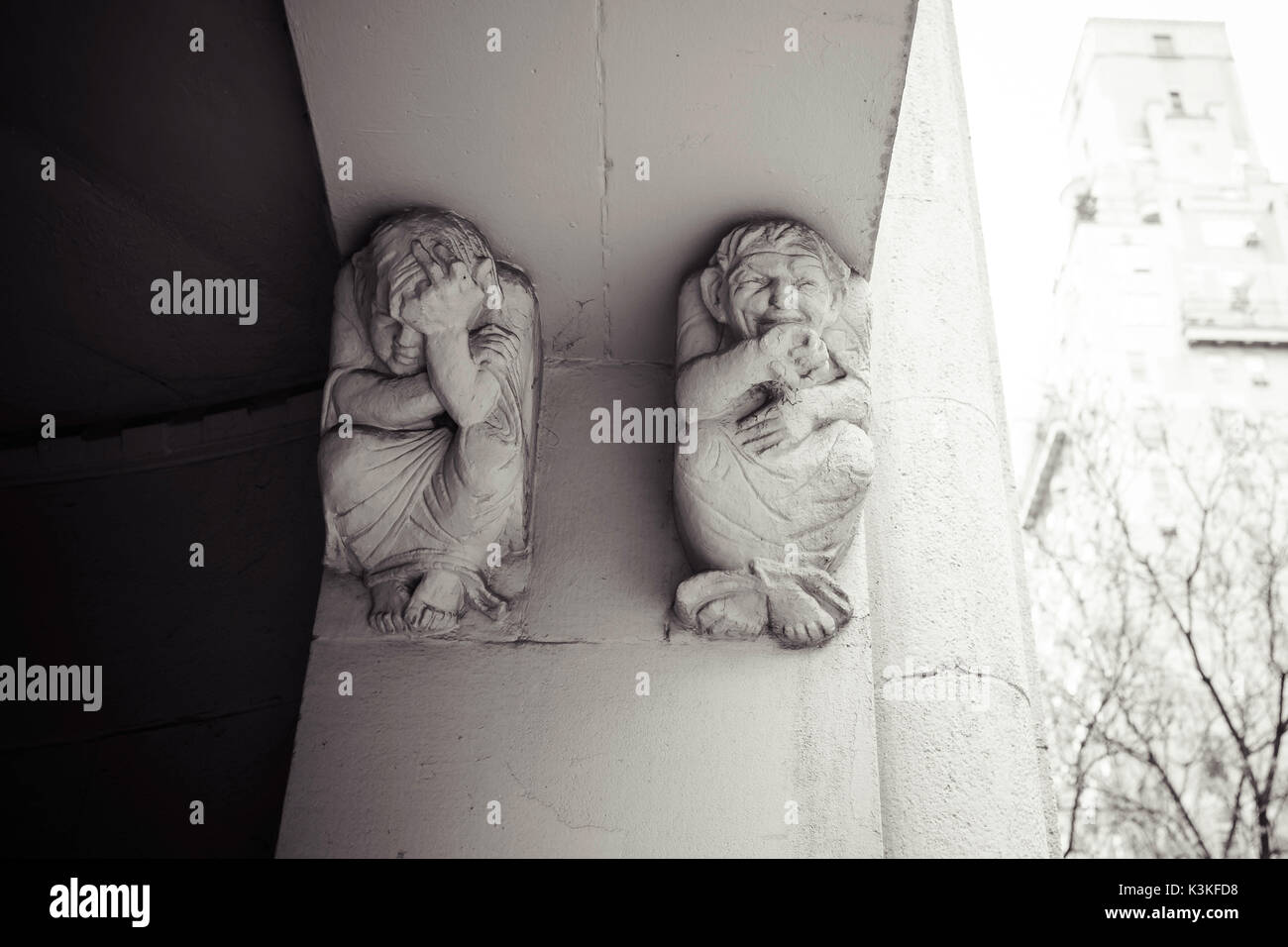 Depressed and laughing stucco sculptures, historic building entrance, Manhatten, New York, USA - Stock Image