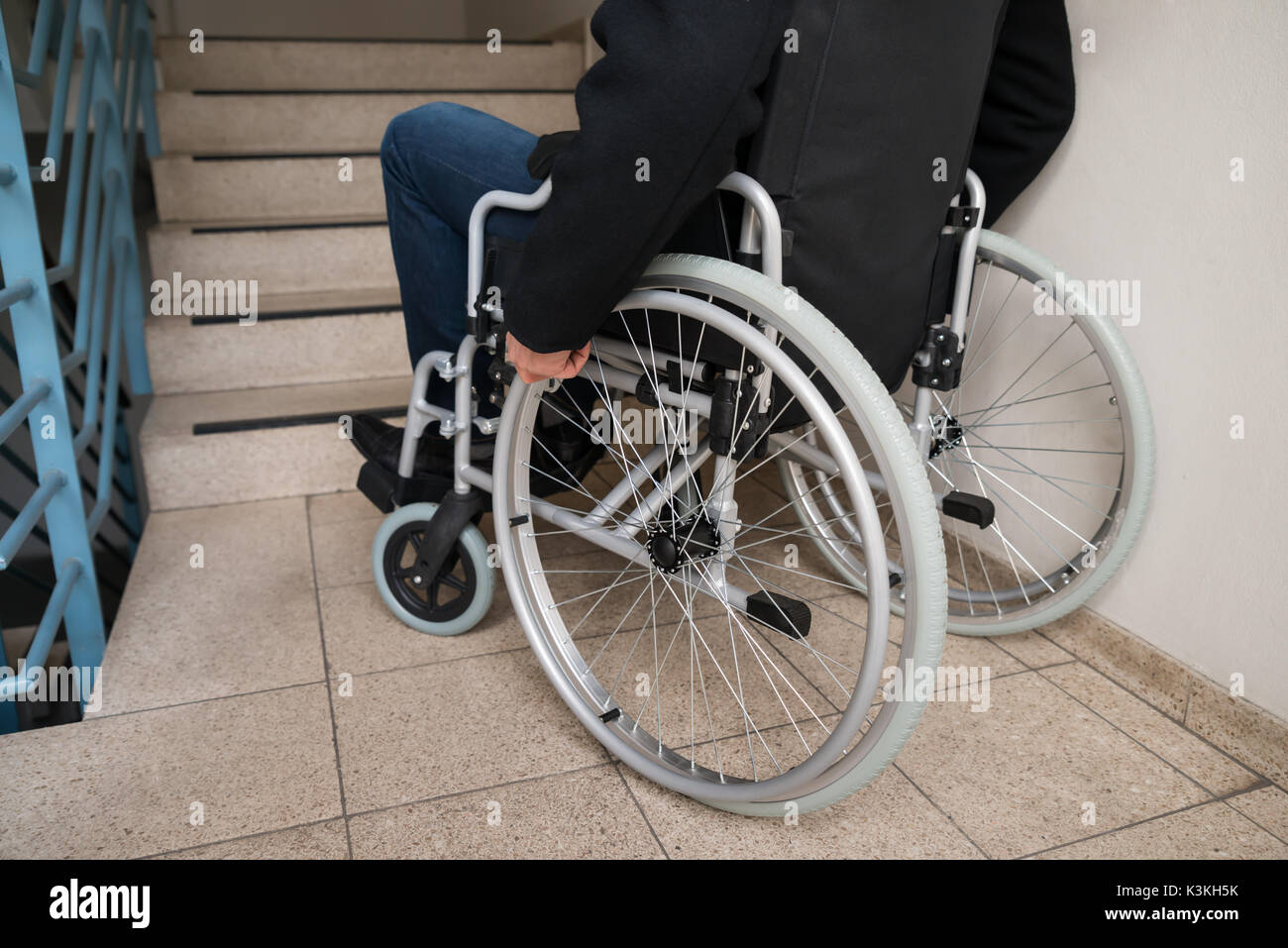 Close-up Of Disabled Man On Wheelchair In Front Of Staircase Stock Photo