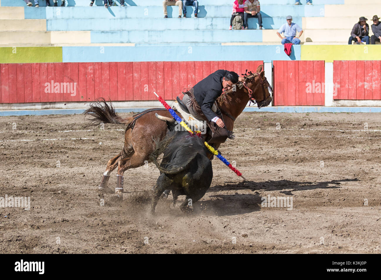 June 18, 2017, Pujili, Ecuador: a bullfighter riding his horse in the arena leaning towards the bull Stock Photo