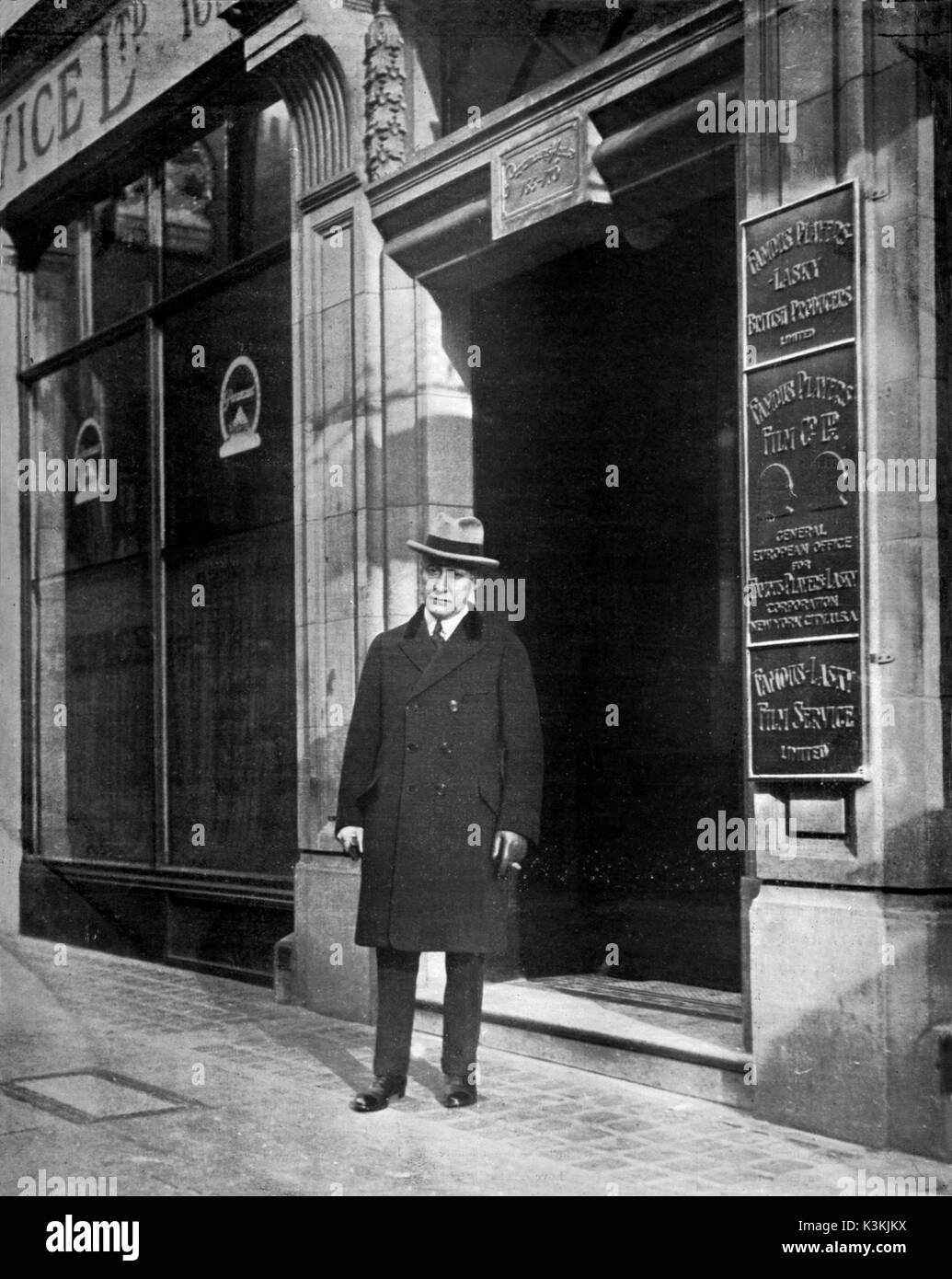 ADOLPH ZUKOR President of The Famous Players-Lasky Corporation outside Paramount House 166-170 Wardour Street, London . The nameplates from the top are for - Famous Players-Lasky British Producers Ltd, Famous Players Film Co Ltd General European Office for Famous Players-Lasky Corporation New York City USA, Famous-Lasky Film Service Ltd - Stock Image