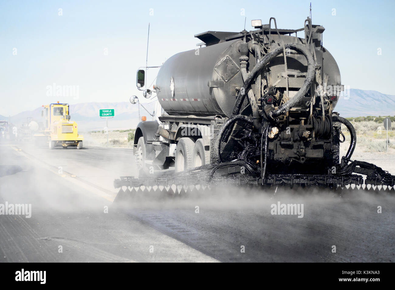 a-black-tanker-truck-spraying-tar-to-res