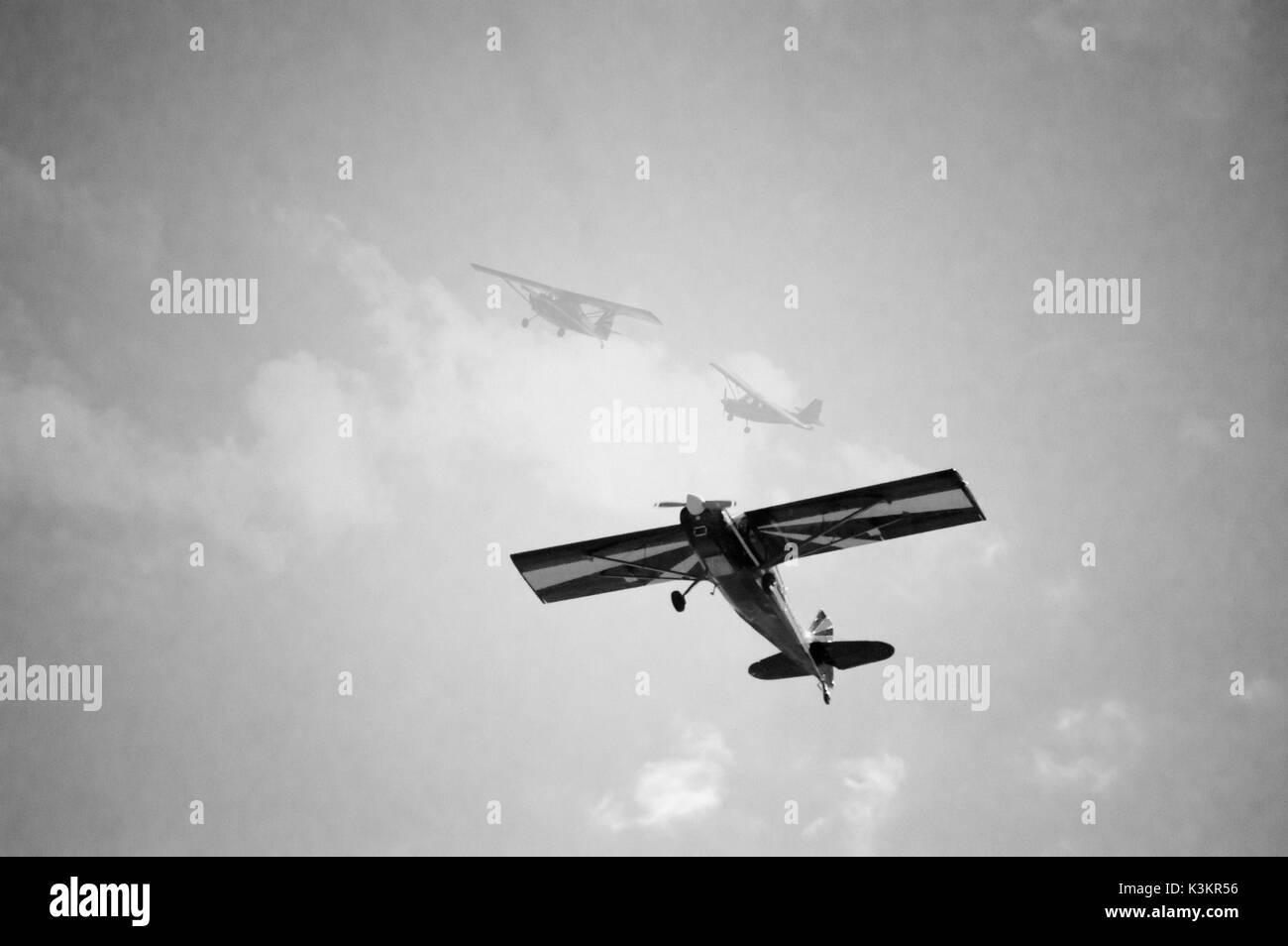 A blue and yellow propeller bi-plane special effects photo showing how it turned in the sky in black and white. - Stock Image
