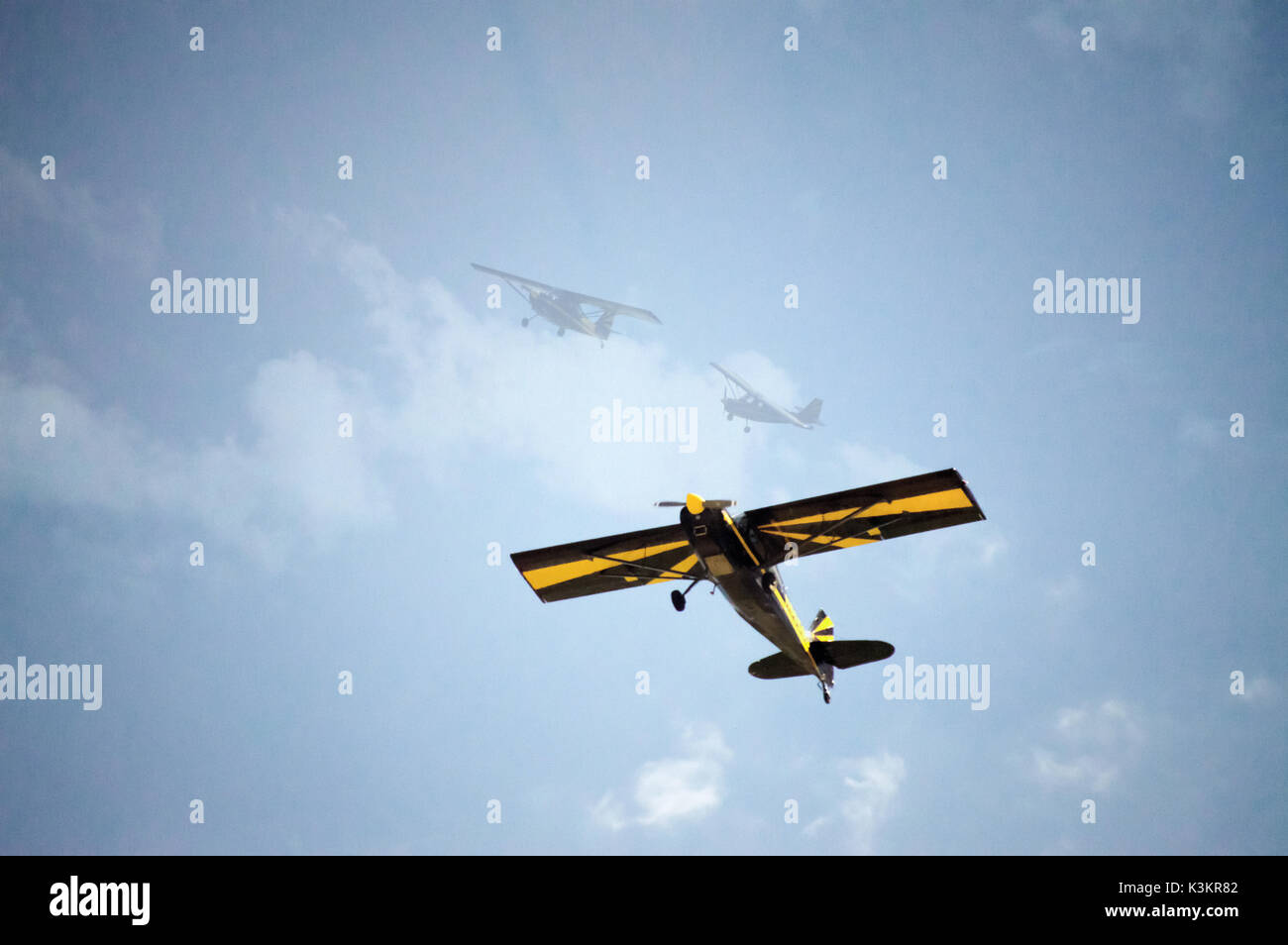 A blue and yellow propeller bi-plane special effects photo showing how it turned in the sky. - Stock Image