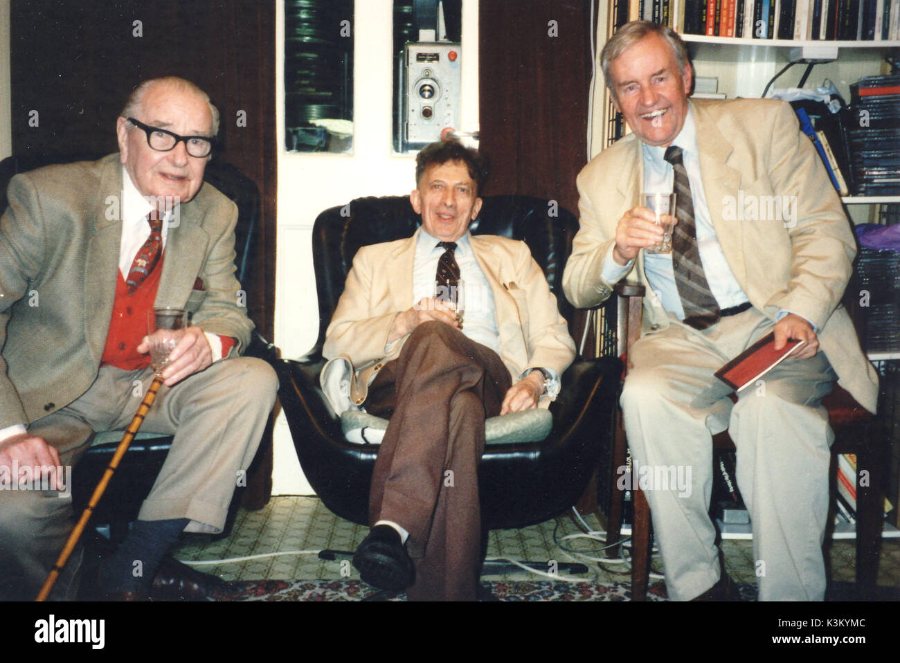 DAVID GILLESPIE [1921 - 2008]  from left - HAROLD FRENCH, actor, producer, theatre and film director, DAVID GILLESPIE film collector, RICHARD BRIERS, actor.  Richard Briers drove his 97 year old friend Harold to film collector David's house in Barnes for Harold to see himself as a young actor in a screening of an original 35mm nitrate print of  the 1932 film 'When London Sleeps', screened on the Westar projector seen behind through the window - Stock Image