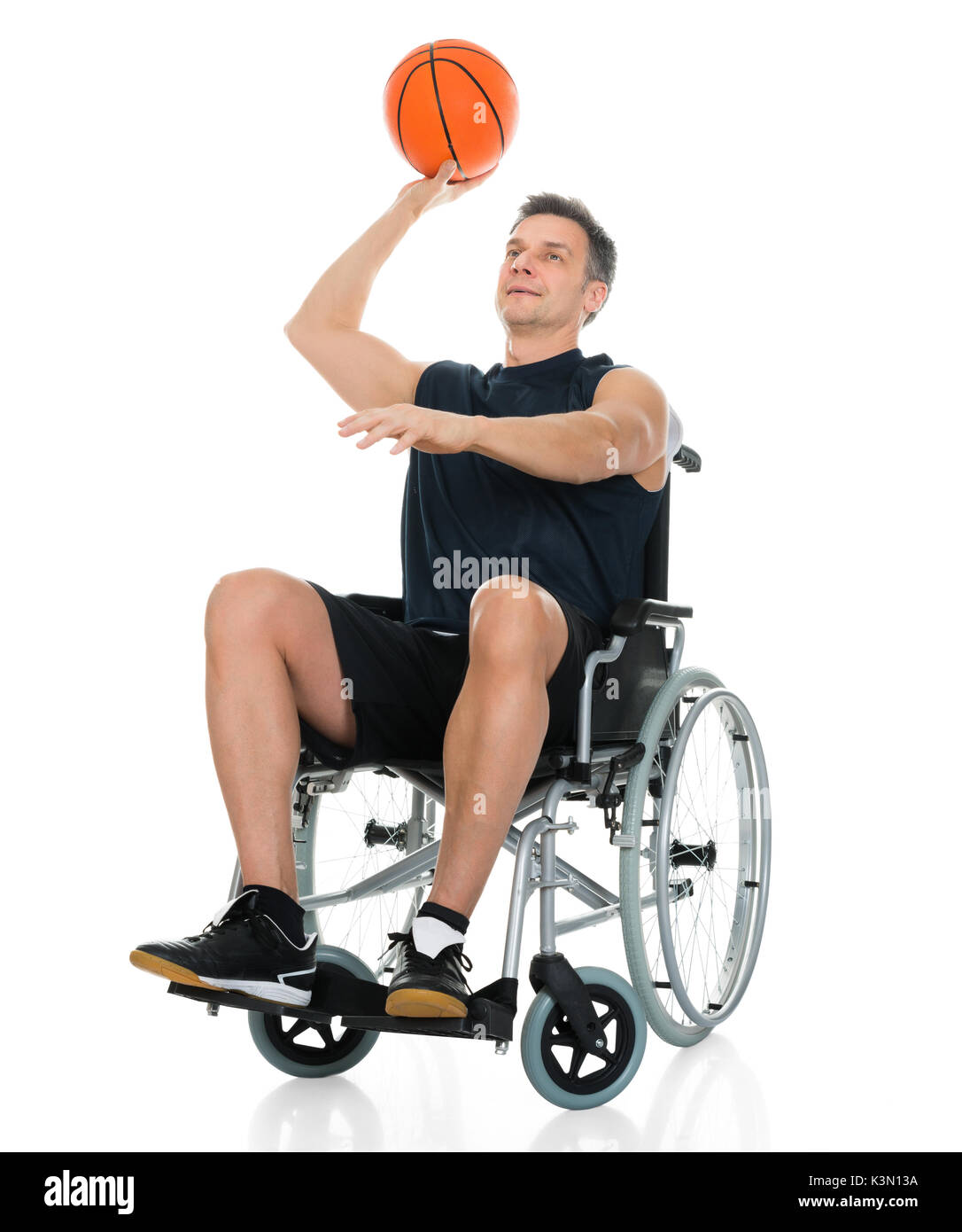 Handicapped Basketball Player On Wheelchair Throwing Ball Over White Background - Stock Image