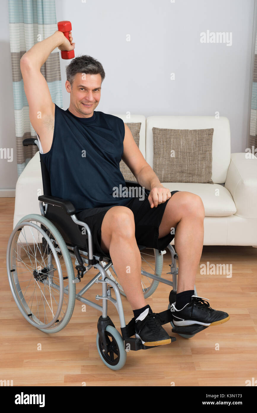 Handicapped Man On Wheelchair Working Out With Dumbbell At Home - Stock Image