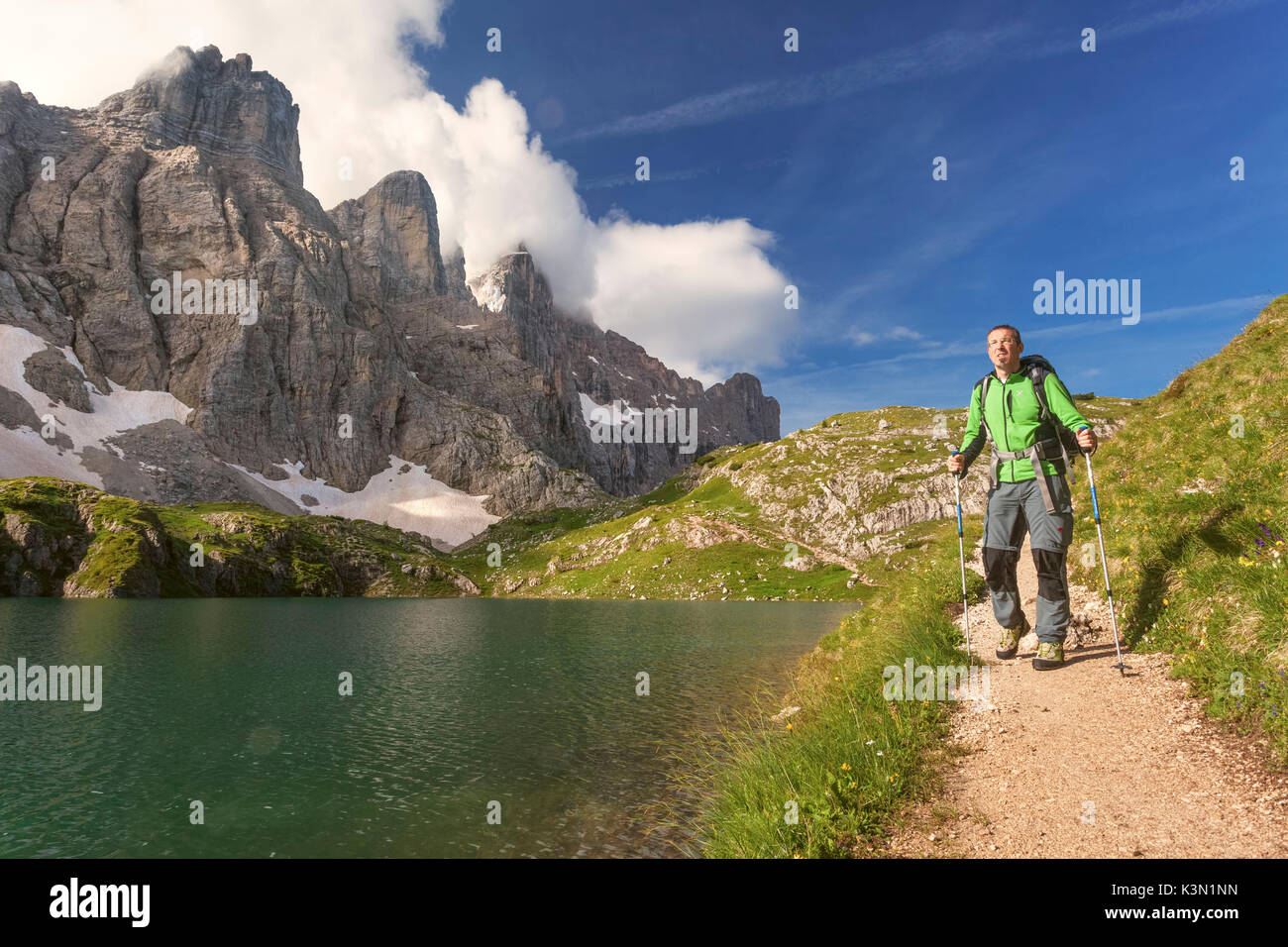 Europe, Italy, Veneto, Belluno. Hiker passes near Lake Coldai along the CAI 560, which at this point coincides with the Alta Via n. 1 of the Dolomites. - Stock Image