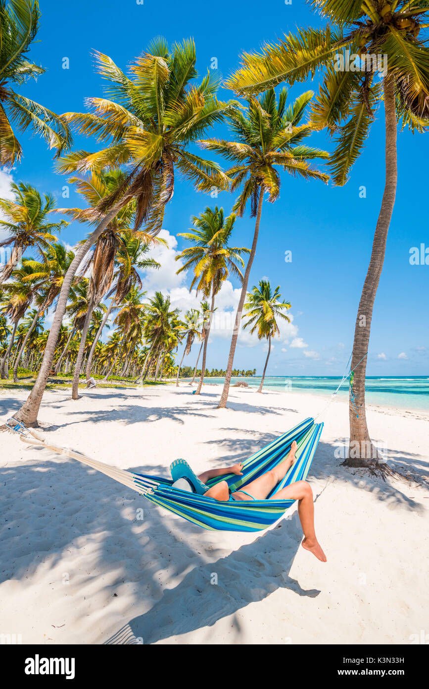 Canto de la Playa, Saona Island, East National Park (Parque Nacional del Este), Dominican Republic, Caribbean Sea. Woman relaxing on a hammock on the beach (MR). - Stock Image