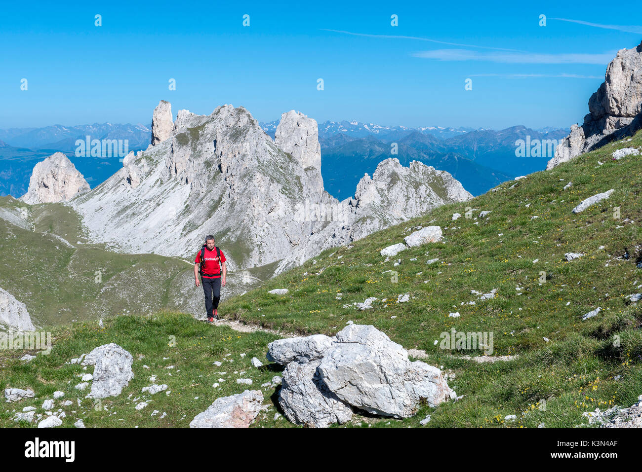 Funes Valley, Dolomites, South Tyrol, Italy. Hiker on the Alta Via Guenther Messner. In the background the peaks of Weisslahn - Stock Image