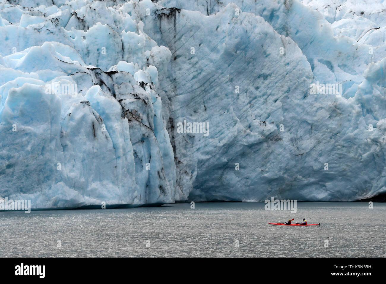 Red canoe (kayak) close to glacier front, Portage glacier, Alaska,USA - Stock Image