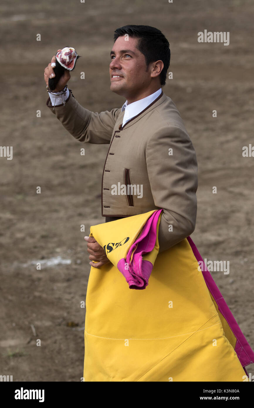 June 18, 2017 Pujili, Ecuador: bullfighter holds up the bulls ear towards the cheering spectators after a succesful fight - Stock Image