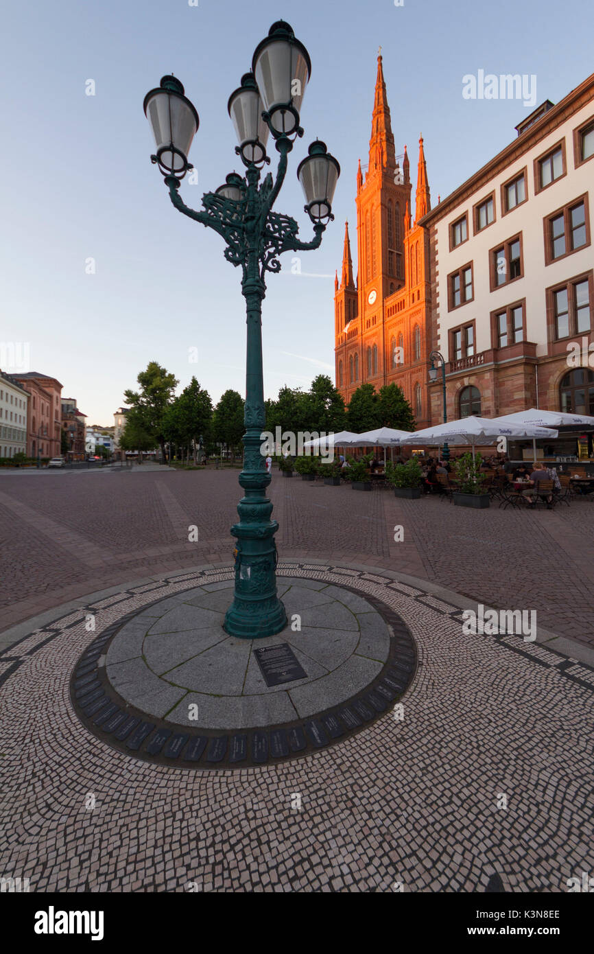 An old street lamp that adorns the square of the Castle and the facade of Marktkirche illuminated by the setting sun. Wiesbaden, Germany - Stock Image
