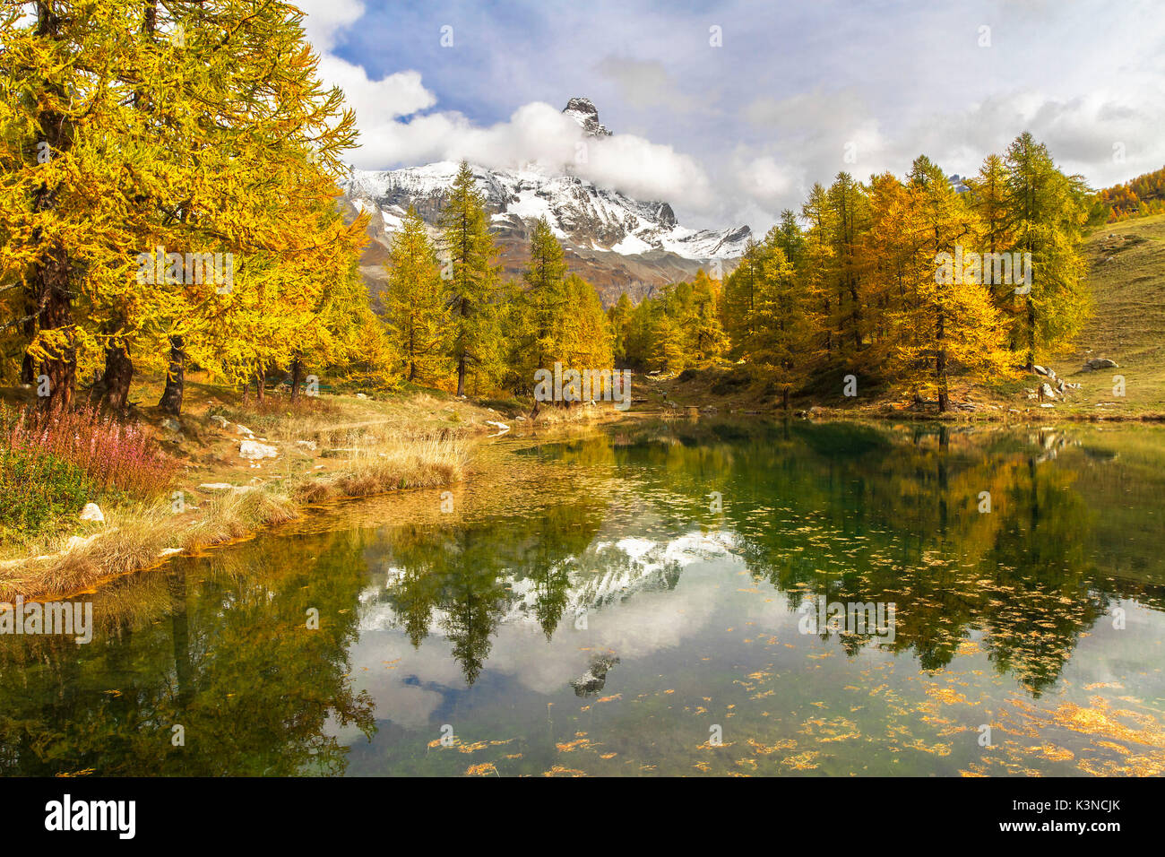 The Matterhorn stands out among the clouds and it is reflected in the small lake Blu surrounded by colorful trees in autumn (Cervinia, Valtournenche, Aosta province, Aosta Valley, Italy, Europe) - Stock Image
