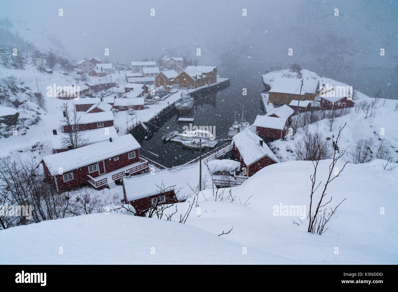 View looking down to snow covered houses in Nusfjord fishing village, Lofoten Islands, Norway - Stock Image