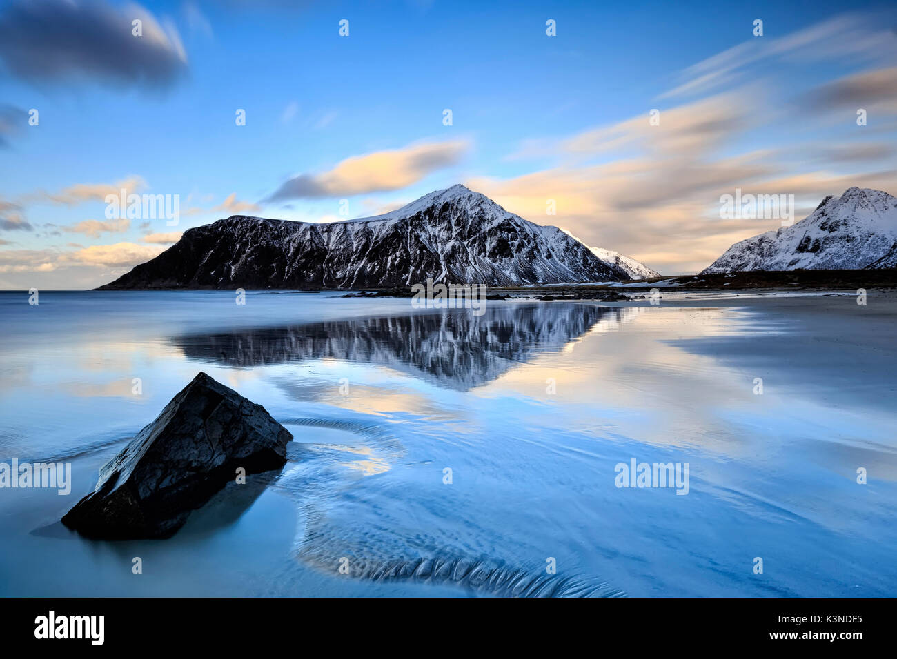 The icy waters of Flakstad Beach reflecting the snowy mountains, Lofoten Islands Skagsanden, Norway - Stock Image