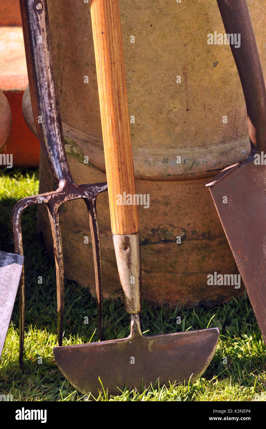 garden tools and axes choppers spades and forks to dig the garden and cultivate gardening experts digging chopping wood and soil gardens logs stoves - Stock Image