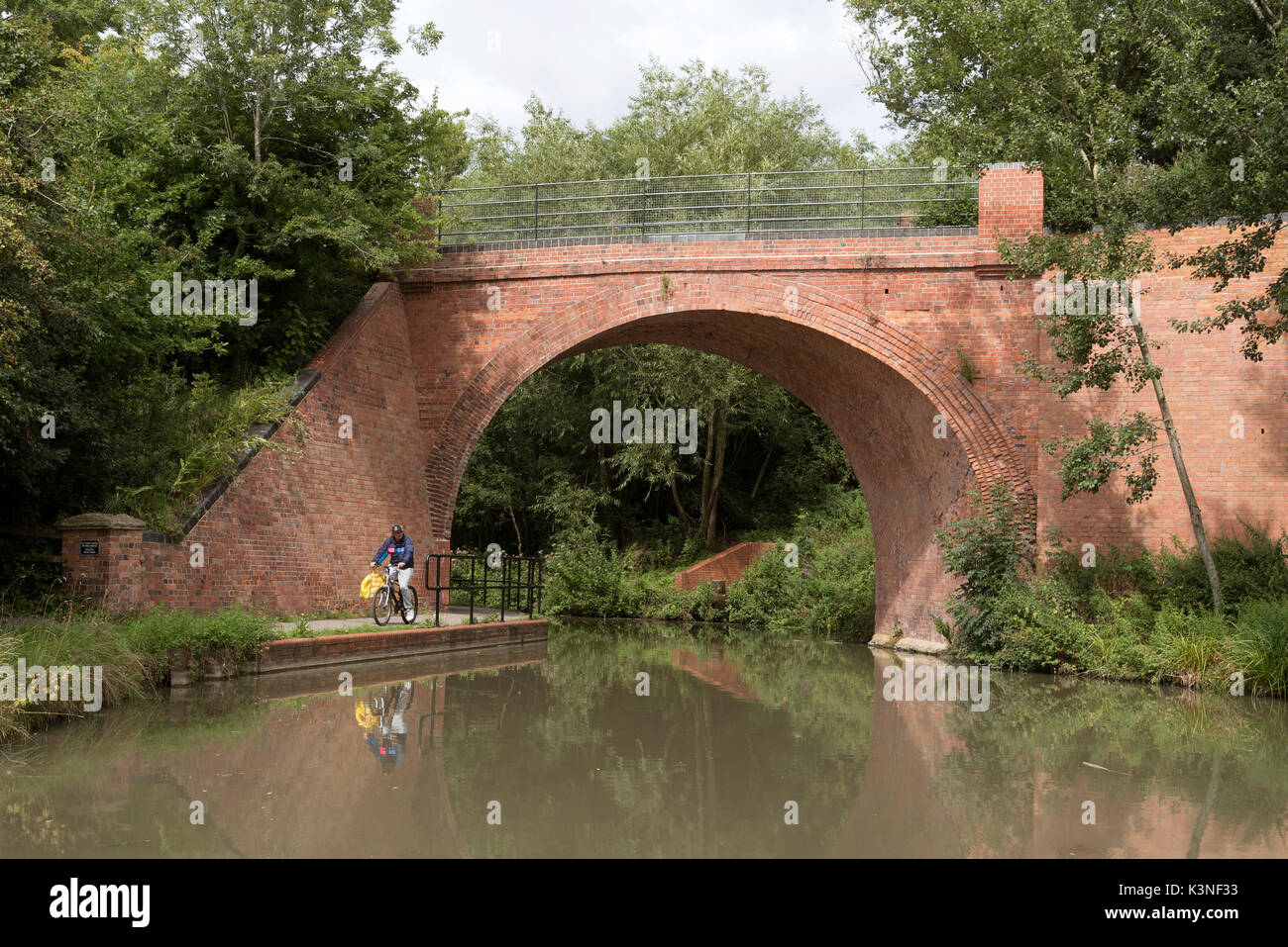 Beavan's Bridge at Westleaze Swindon UK. August 2017. Man riding a cycle on the towpath under the brick built bridge crossing the recently restored Wi - Stock Image