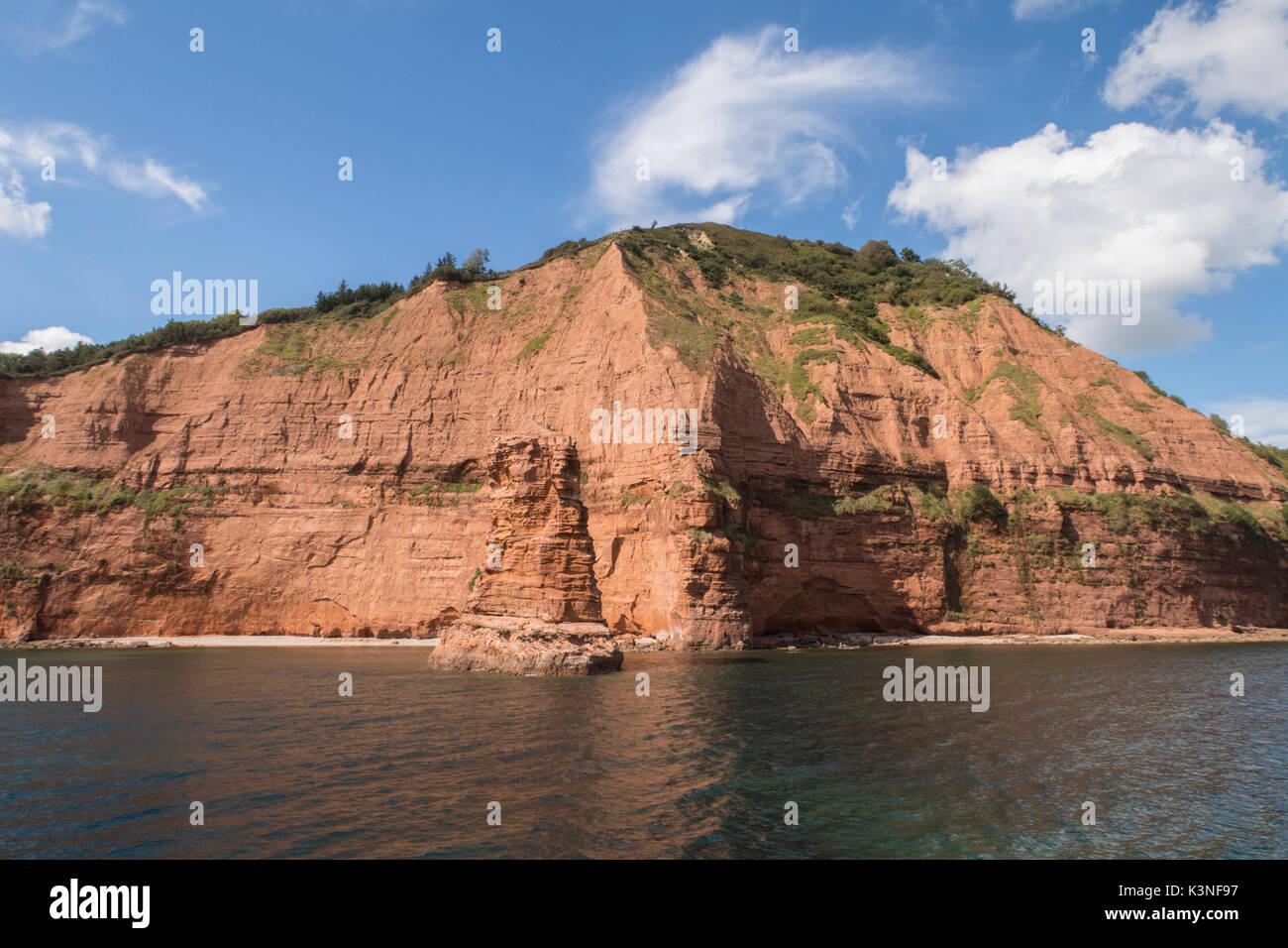 High Peak rises above a triassic rock stack near Ladram Bay, Sidmouth, Devon. - Stock Image