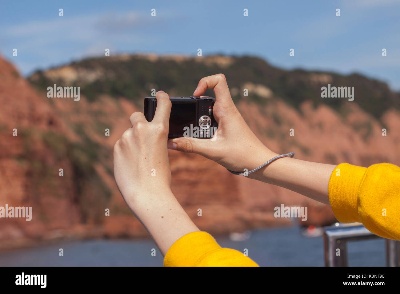A pair of hands taking pictures of a seaside cliff face with a digital camera. - Stock Image