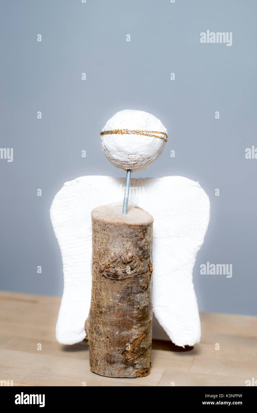 Angel made of plaster and wood with golden headband - Stock Image
