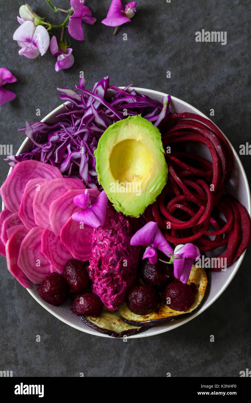 Vegan bowl with raw and cooked beetroot , red cabbage, aubergine - Stock Image