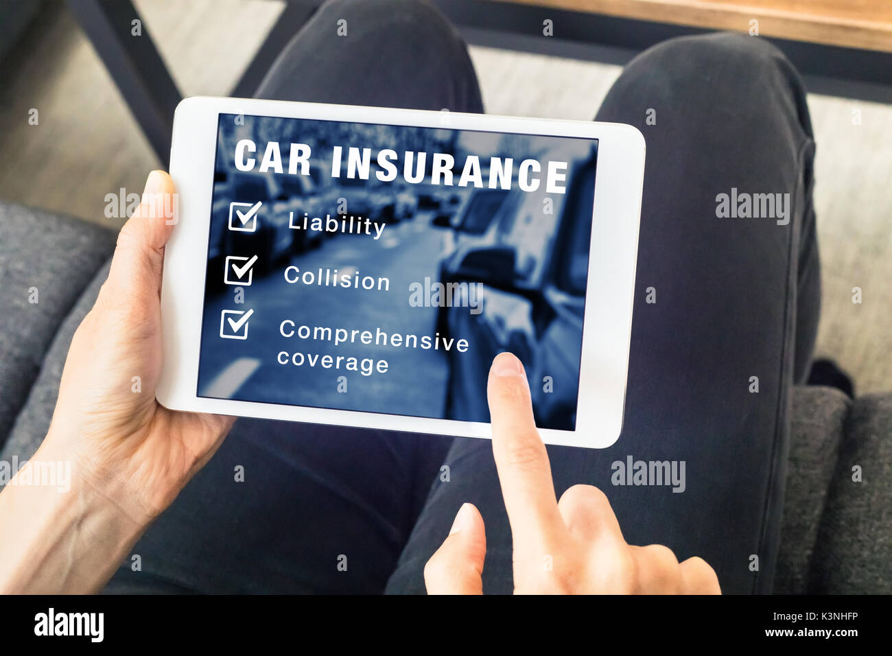 Person choosing car insurance coverage options (liability, collision, comprehensive) on website on digital tablet computer screen, vehicle and risk pr - Stock Image
